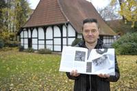 Museumsleiter Michael Strauß mit einem Buch über die Arbeiten von Dr. Hermann Reichling. Die Bilder des Fotografen und Naturschützers sind vom 10. Dezember bis zum 4. April im Bünder Museum zu sehen